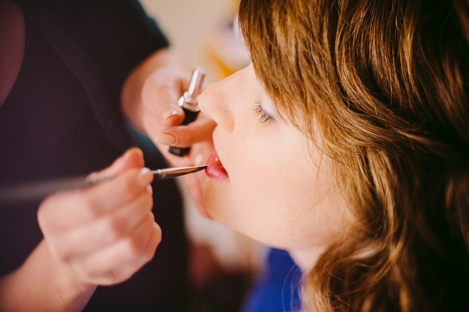 The bride's sister has makeup applied