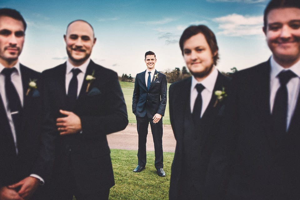 Groom and groomsmen posing in front of the golf course