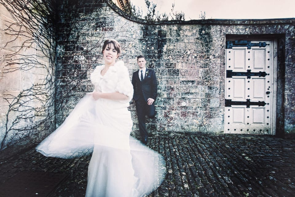 Bride dances in front of groom in the courtyard at Bowood House