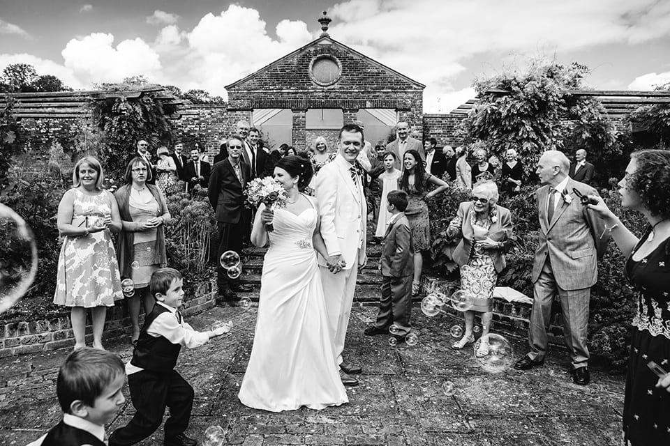 bride and groom standing as guests low bubbles and children running