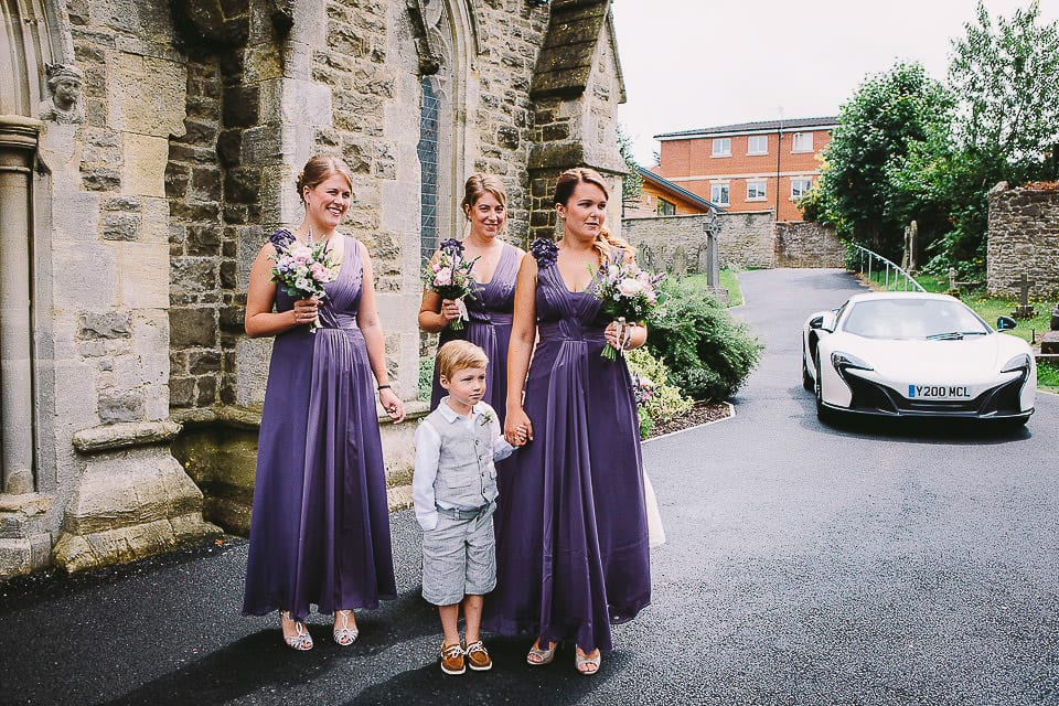 Bridesmaids and page boy waiting on the steps of Christ Church for the bride