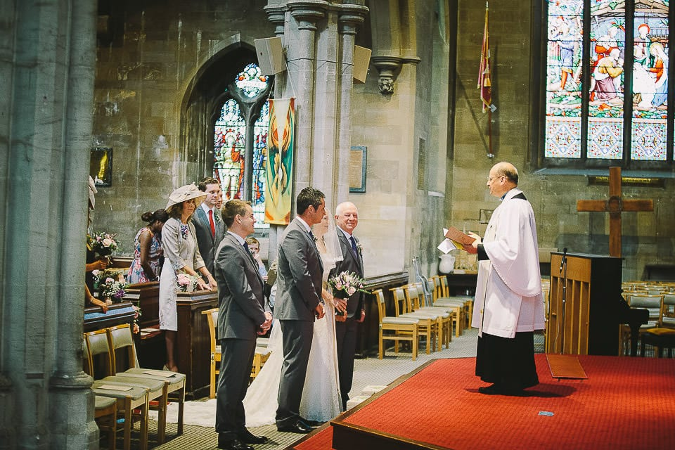 Bride and groom standing in the church with father of the bride and best man