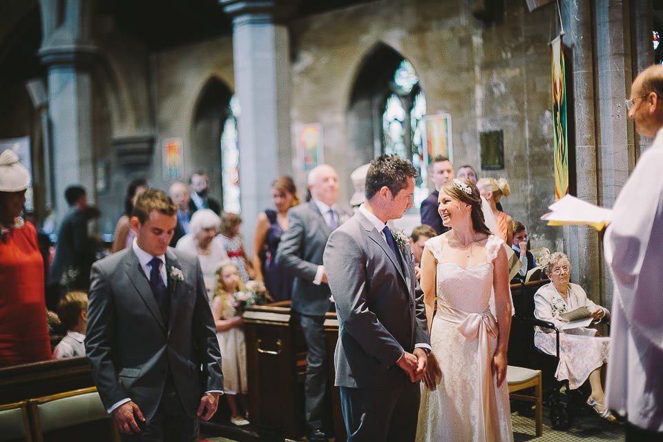 Bride looks back over her shoulder at her family during wedding ceremony