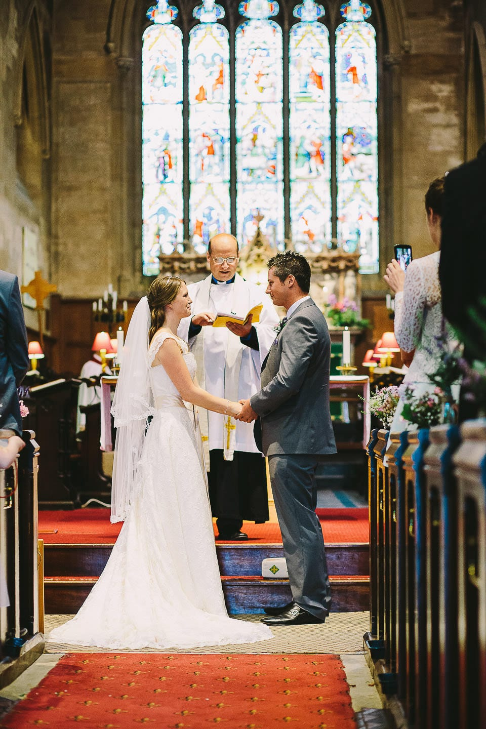 Bride and groom holding hands in church