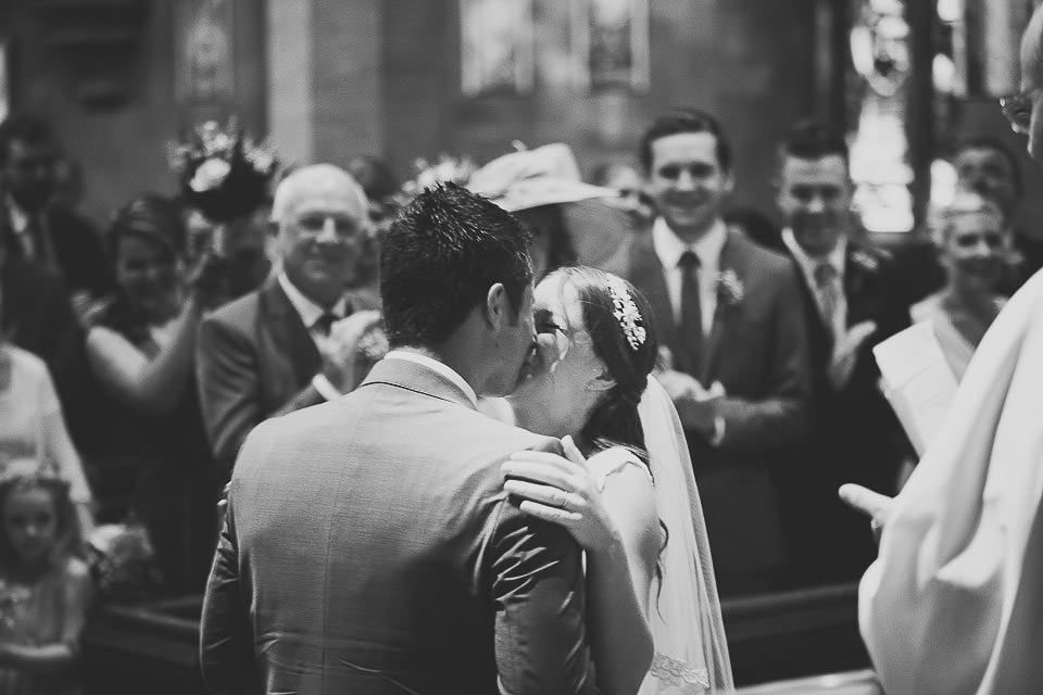 Bride and groom having their first kiss in church