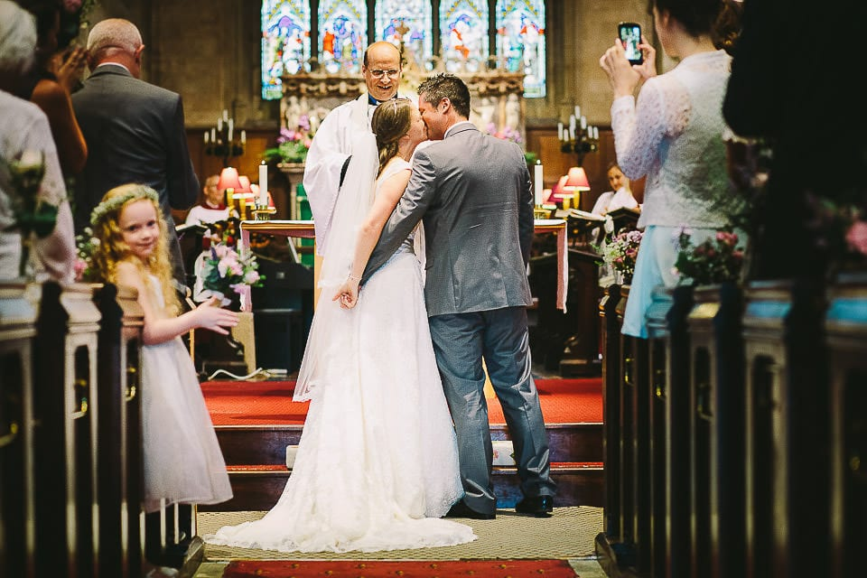 Full length image of the bride and groom having their first kiss