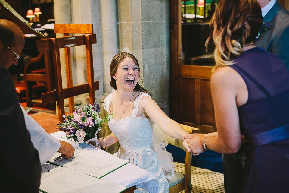 Bride holding hands with her bridesmaid in Christ Church