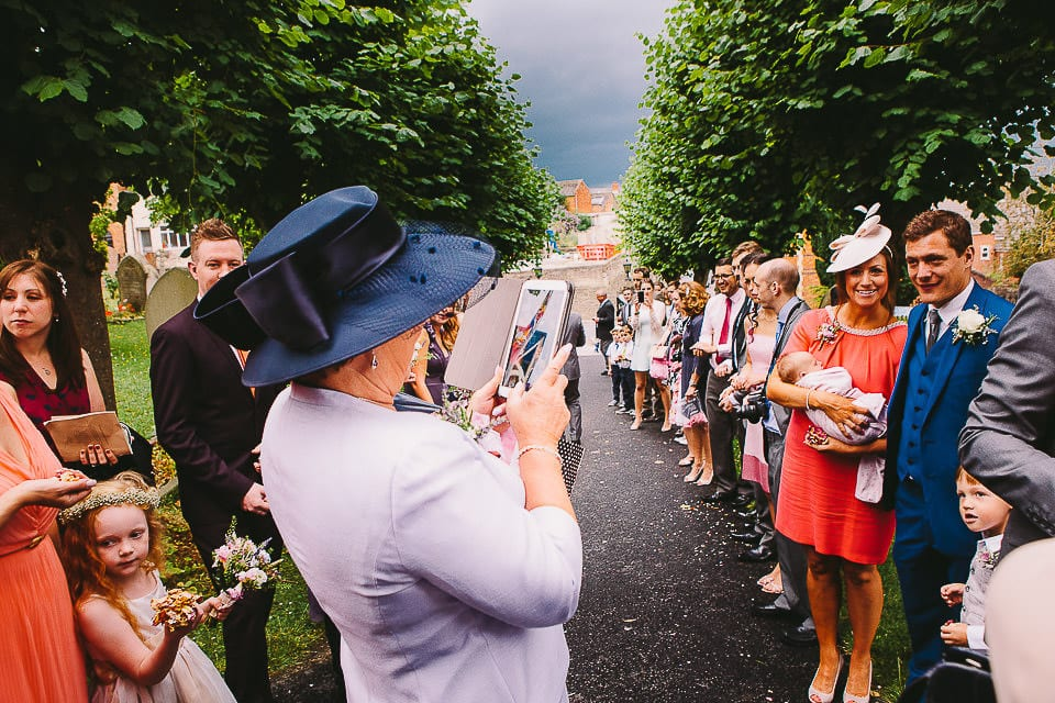 Guests lined up either side of the path to throw confetti on bride and groom
