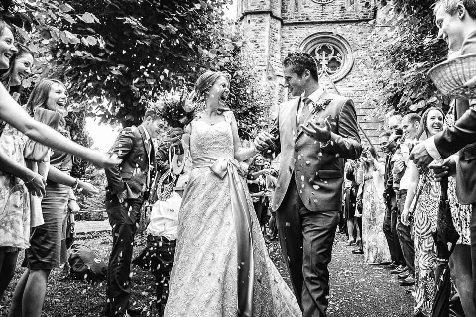 Black and white image of bride and groom walking through confetti