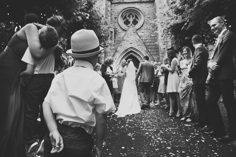 Bride and groom walk back up the church path after confetti