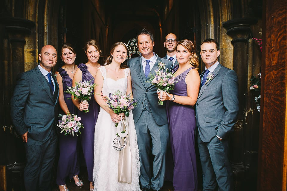 Bride and groom with groomsmen and bridesmaids in church doorway