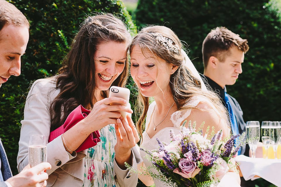 Bride and a friend looking at phone pictures at Abbey House Gardens