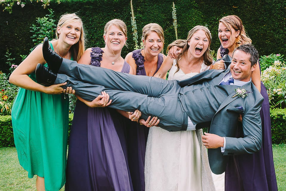Bride and bridesmaids holding up the groom at Abbey House Gardens