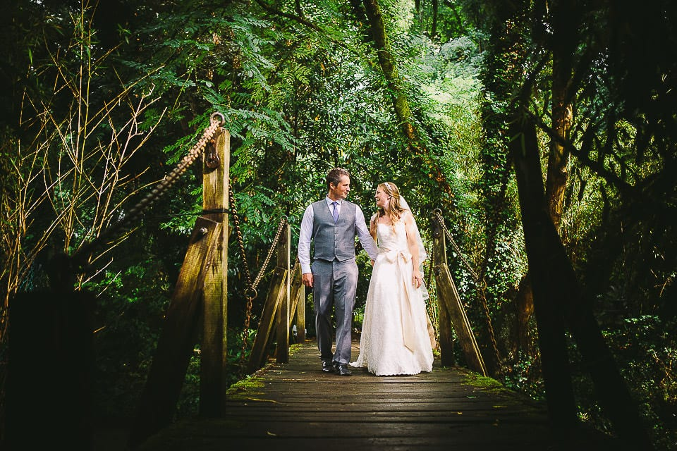 Portrait of bride and groom walking across the bridge at Abbey House Gardens