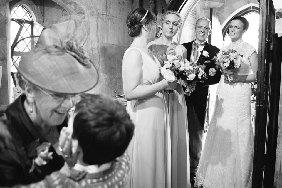 Black and white image of bridal party waiting in church foyer