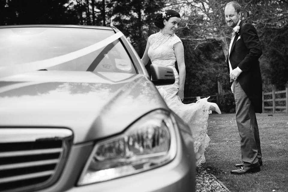 Black and white image of bride showing groom sixpence on her shoe by wedding car