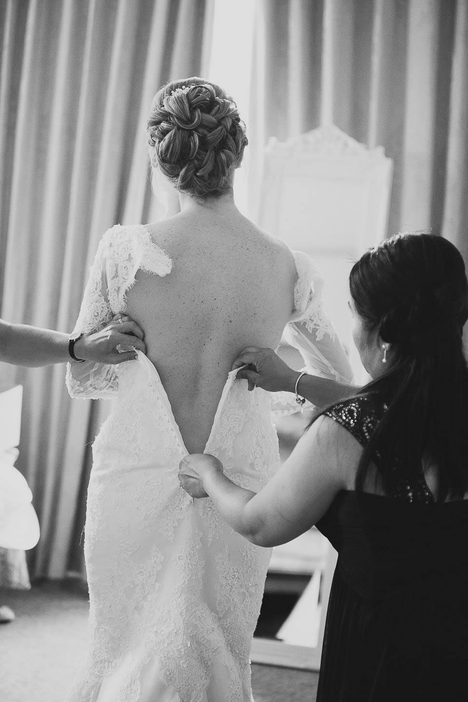 Bride being helped into her wedding dress at Bath Spa Hotel
