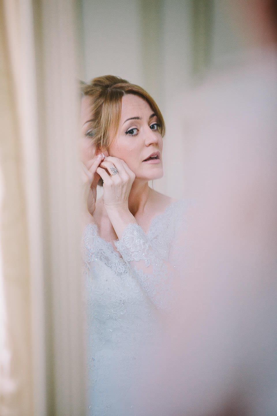 Bride putting on her earrings in the mirror at Bath Spa Hotel