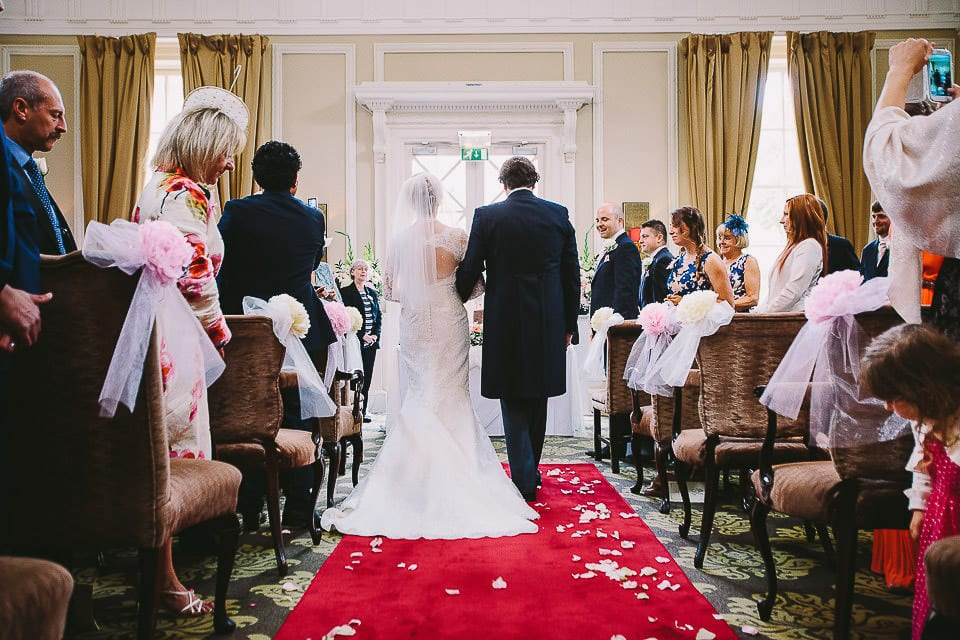 View of bride and her brother from the rear walking up the aisle at Bath Spa Hotel