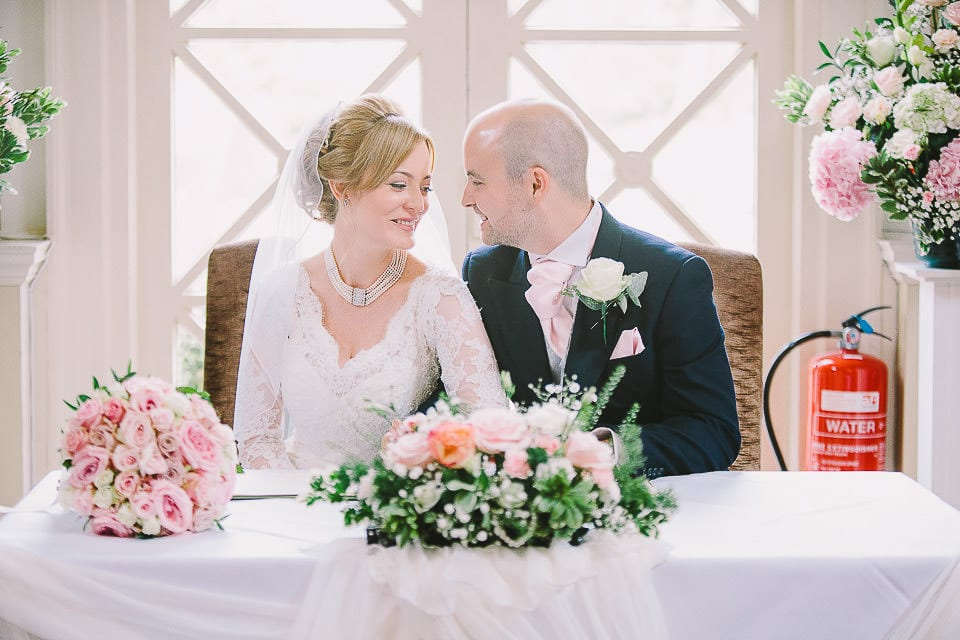 Bride and groom seated to sign the register at Bath Spa Hotel