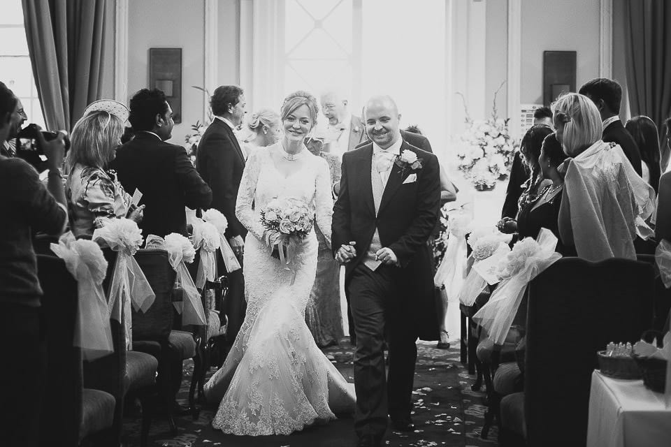 Black and white image of bride and groom walking down the aisle at Bath Spa Hotel
