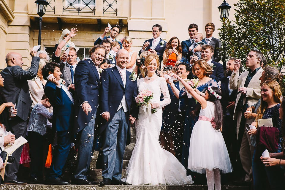 Guests throw confetti over bride and groom outside at Bath Spa Hotel