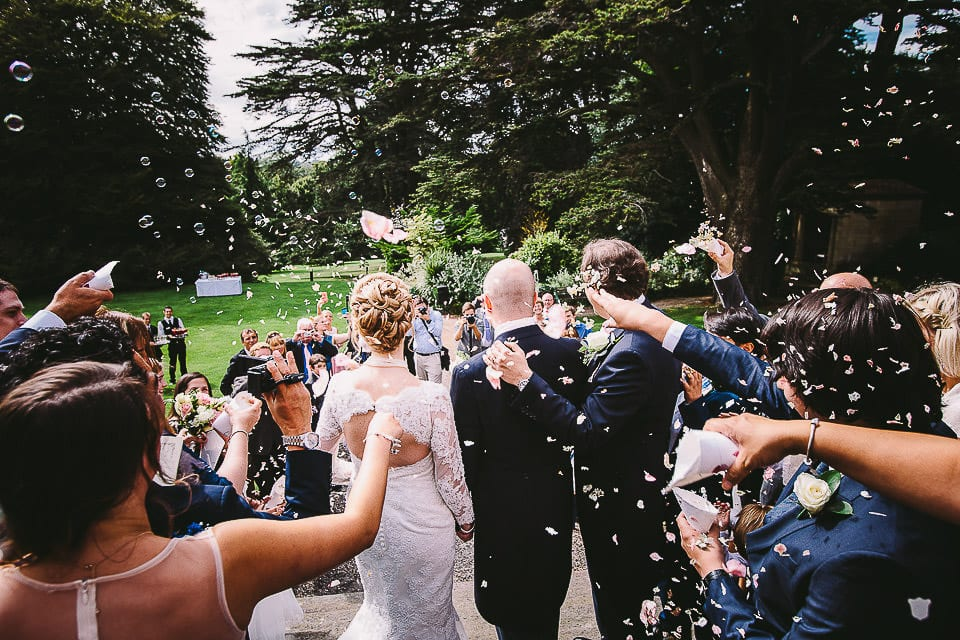 View from the rear of guests showering bride and groom with confetti