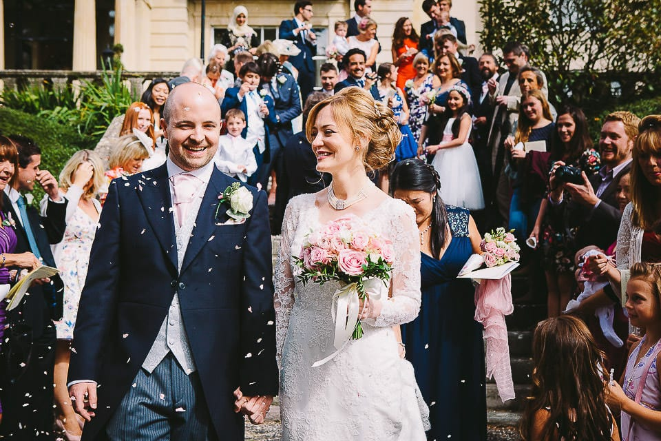 Bride and groom walk through confetti on the steps outisde at Bath Spa Hotel