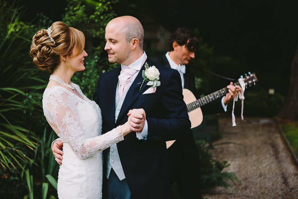 Bride and groom dancing to guitar player in the gardens at Bath Spa Hotel