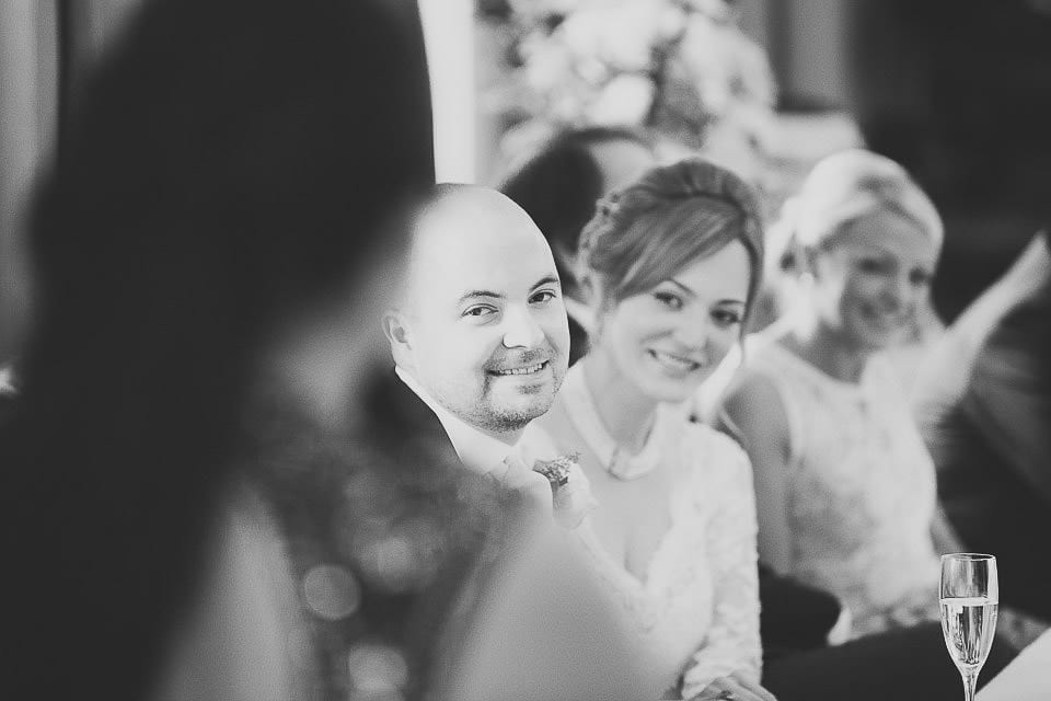 Black and white image of bride and groom listening to speeches at Bath Spa Hotel