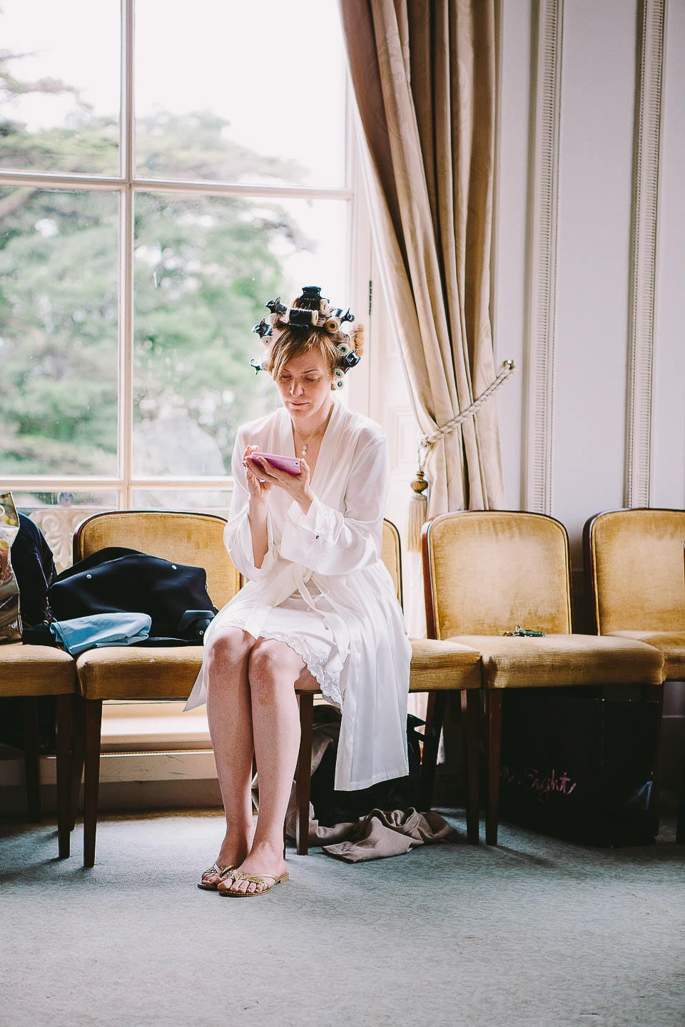 Bride sending a message on her phone at at Bath Spa Hotel