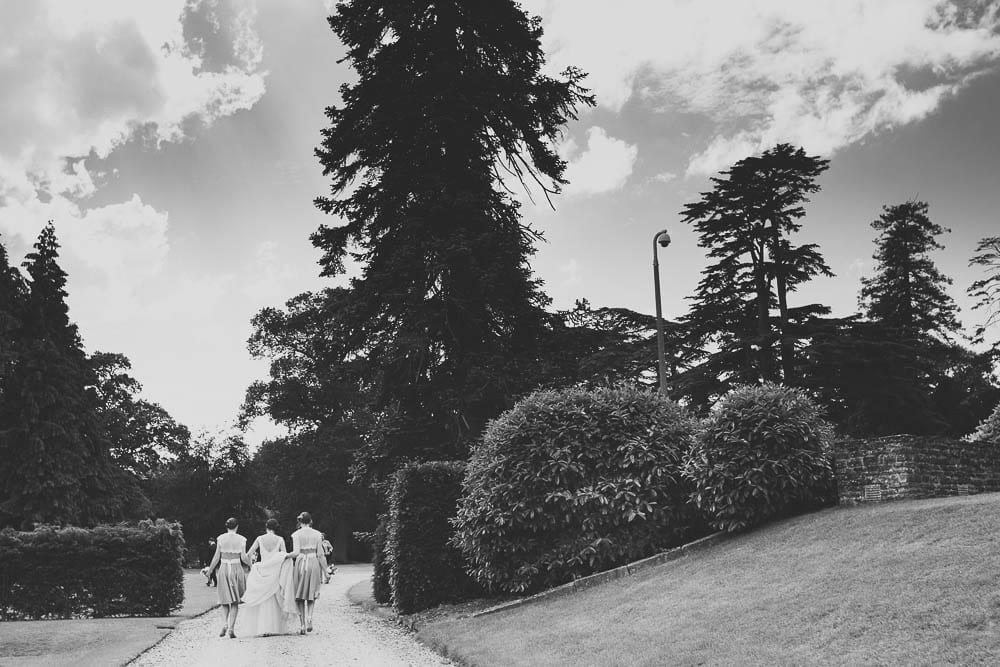 Black and white image of bride and bridesmaids walking in gardens of Grittleton House