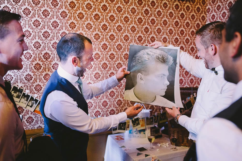 Groom being presented with funny photos by his friends at Grittleton House