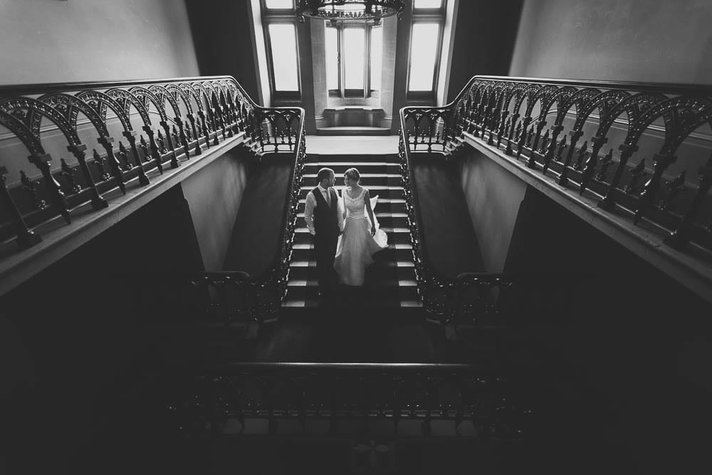 Bride and groom walking down the grand staircase at Grittleton House