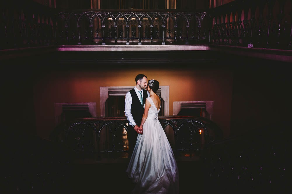 Portrait of bride and groom on the grand staircase at Grittleton House