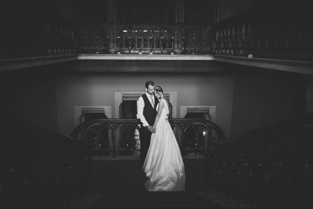 Black and white portrait of the bride and groom on the stairs in Grittleton House