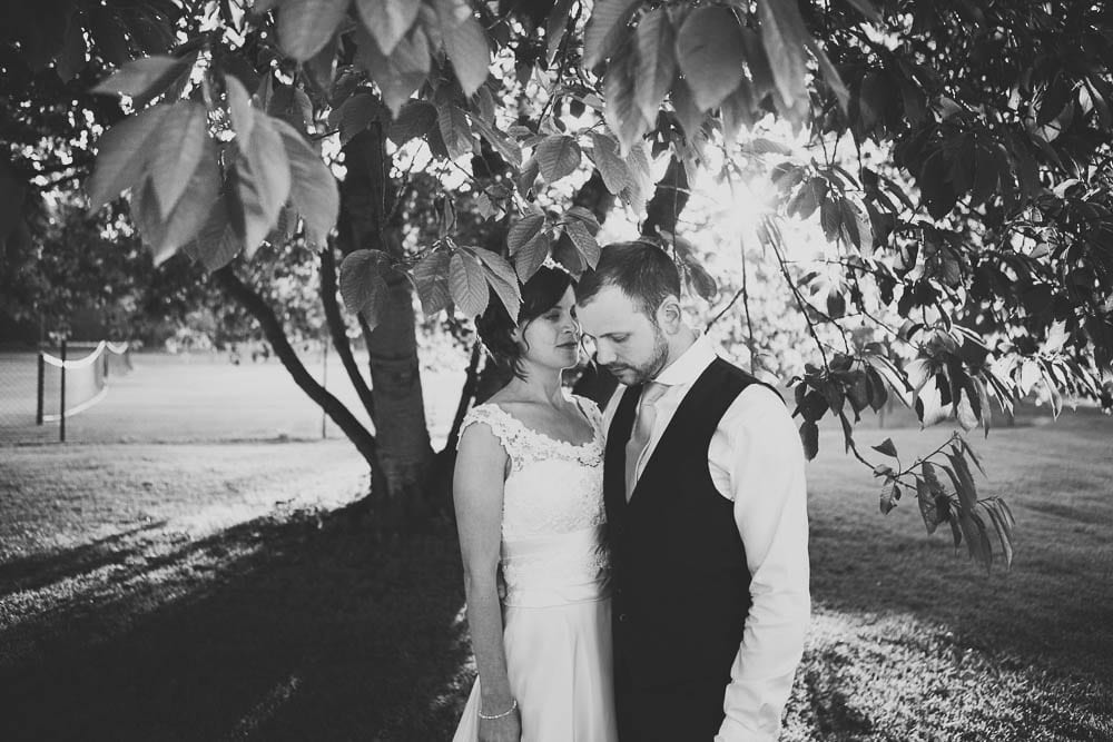 Bride and groom under a tree in the gardens of Grittleton House