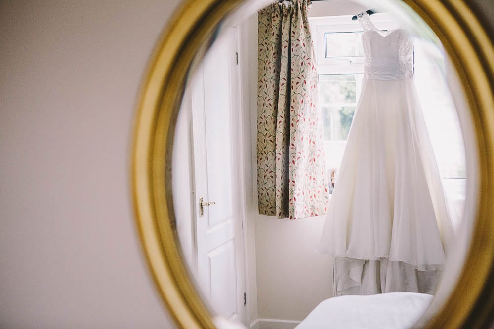 View of the hanging wedding dress in the mirror