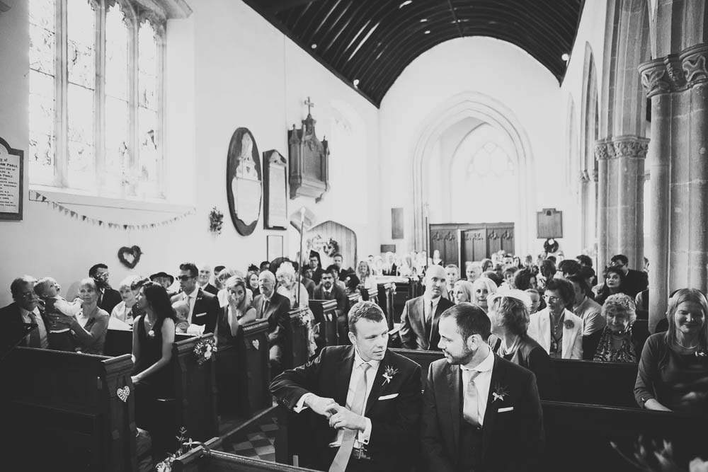 Black and white image of the guests seated inside Great Somerford Church