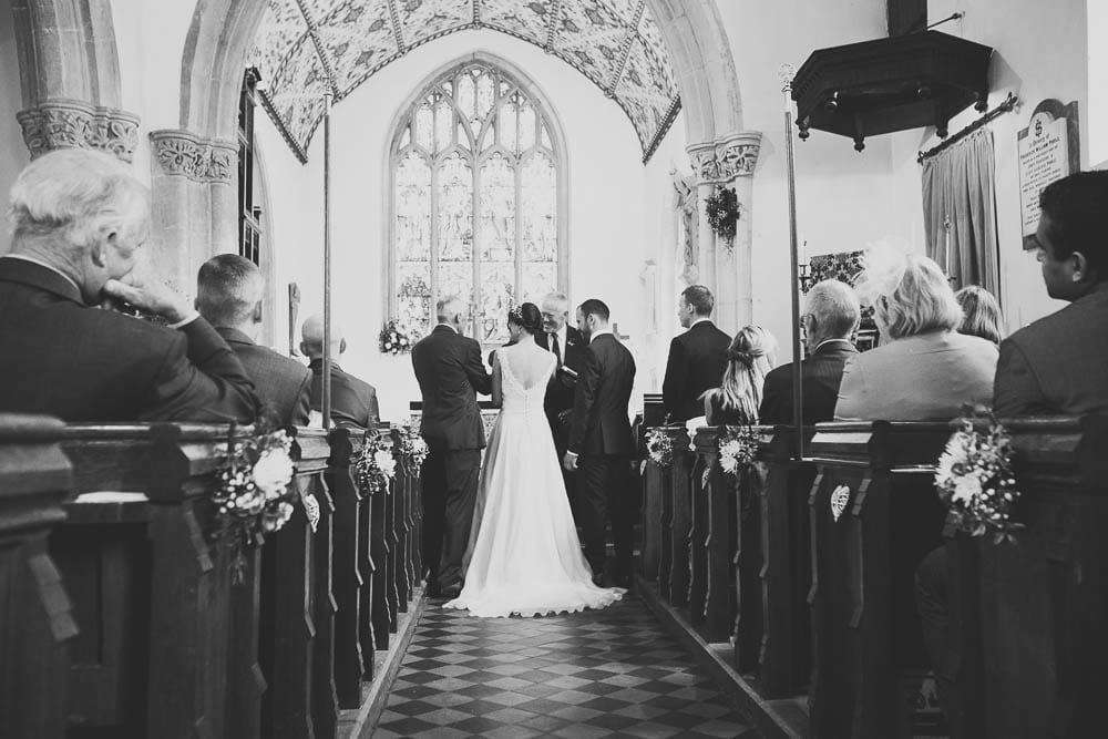 Black and white view down the aisle from the back of Great Somerford church