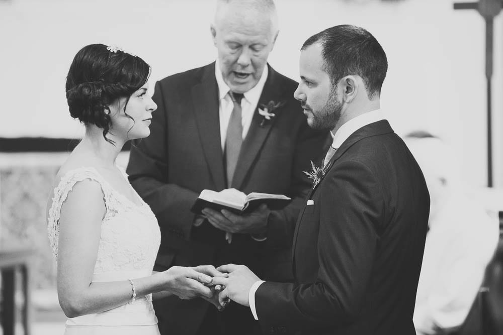 Black and white image of bride and groom exchanging rings in church