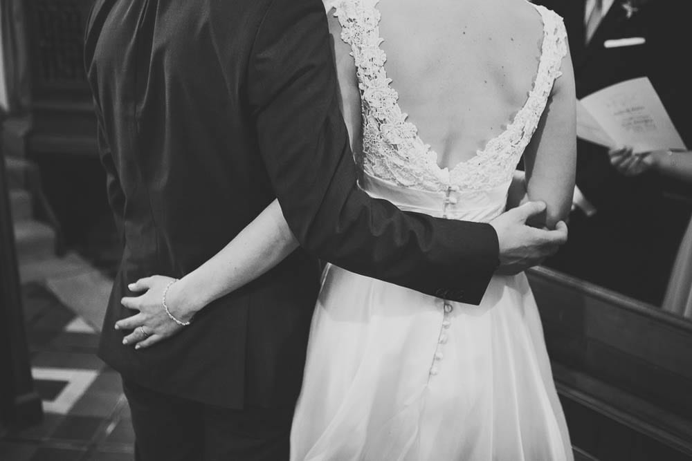 Black and white image of bride and groom with their arms around each other