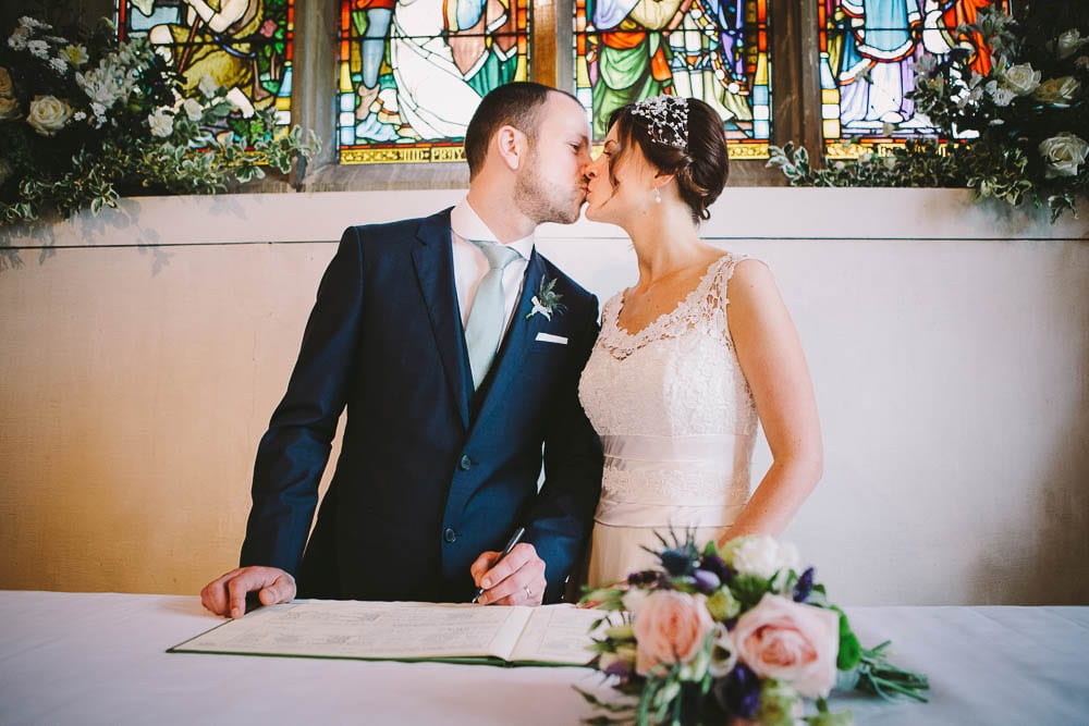 Bride and groom kissing at the signing of the register in Great Somerford Church