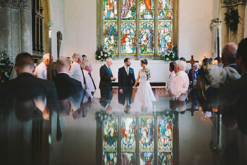 Reflection shot of bride and groom at the alter in Great Somerford church