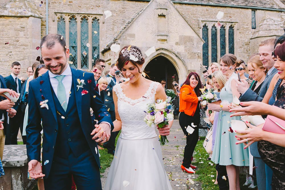 Bride and groom walking through confetti at Great Somerford church