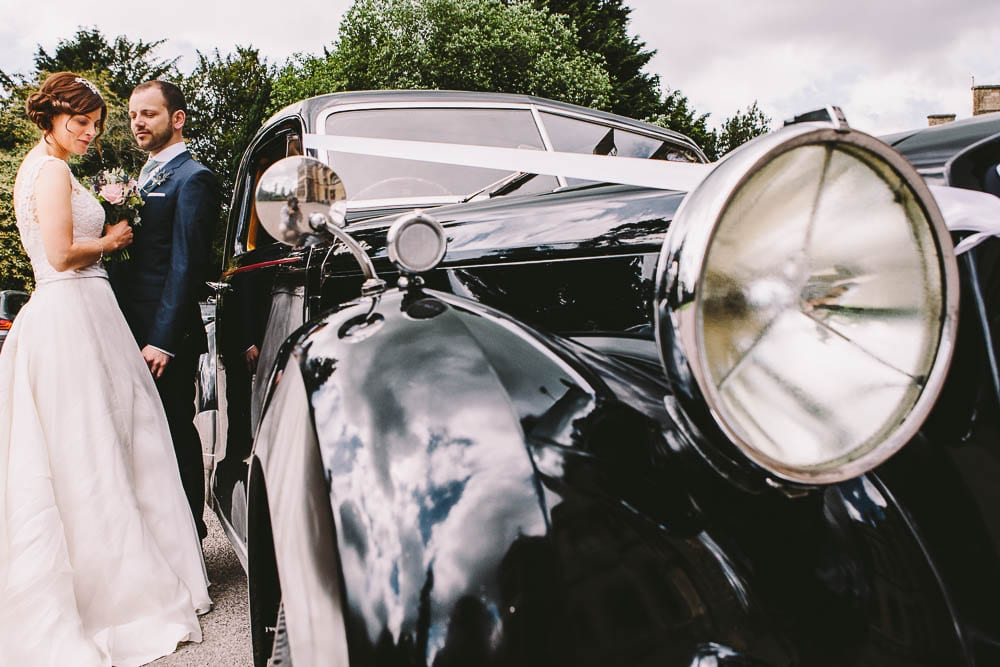 Portrait of bride and groom by the wedding car outside Grittleton House
