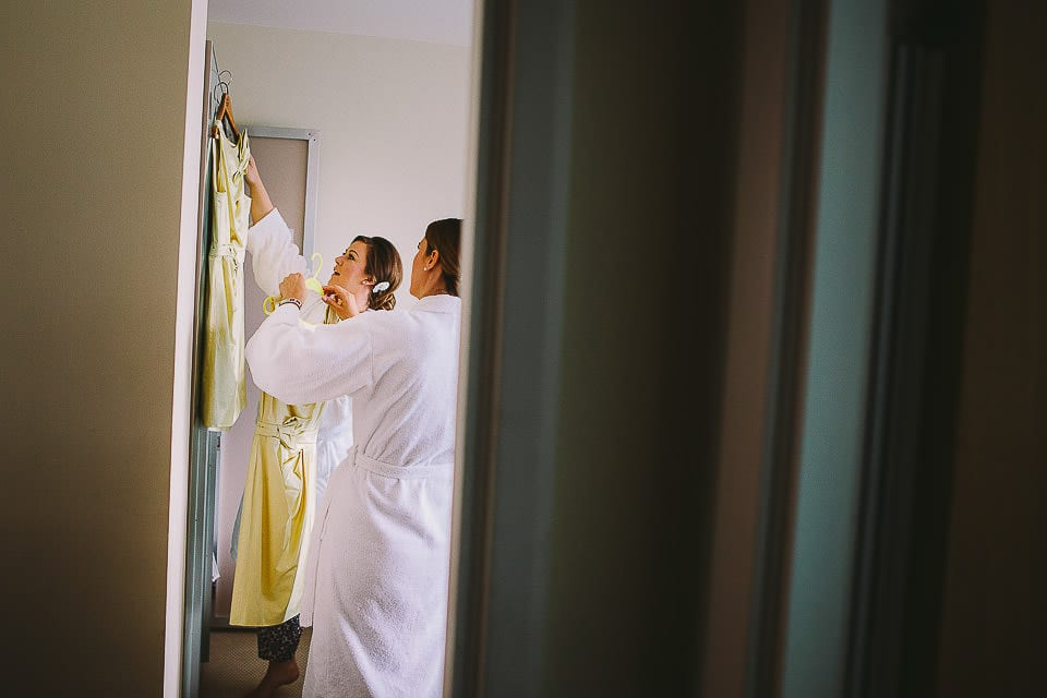 Bridesmaids hanging up their dresses at The Captains Club Hotel