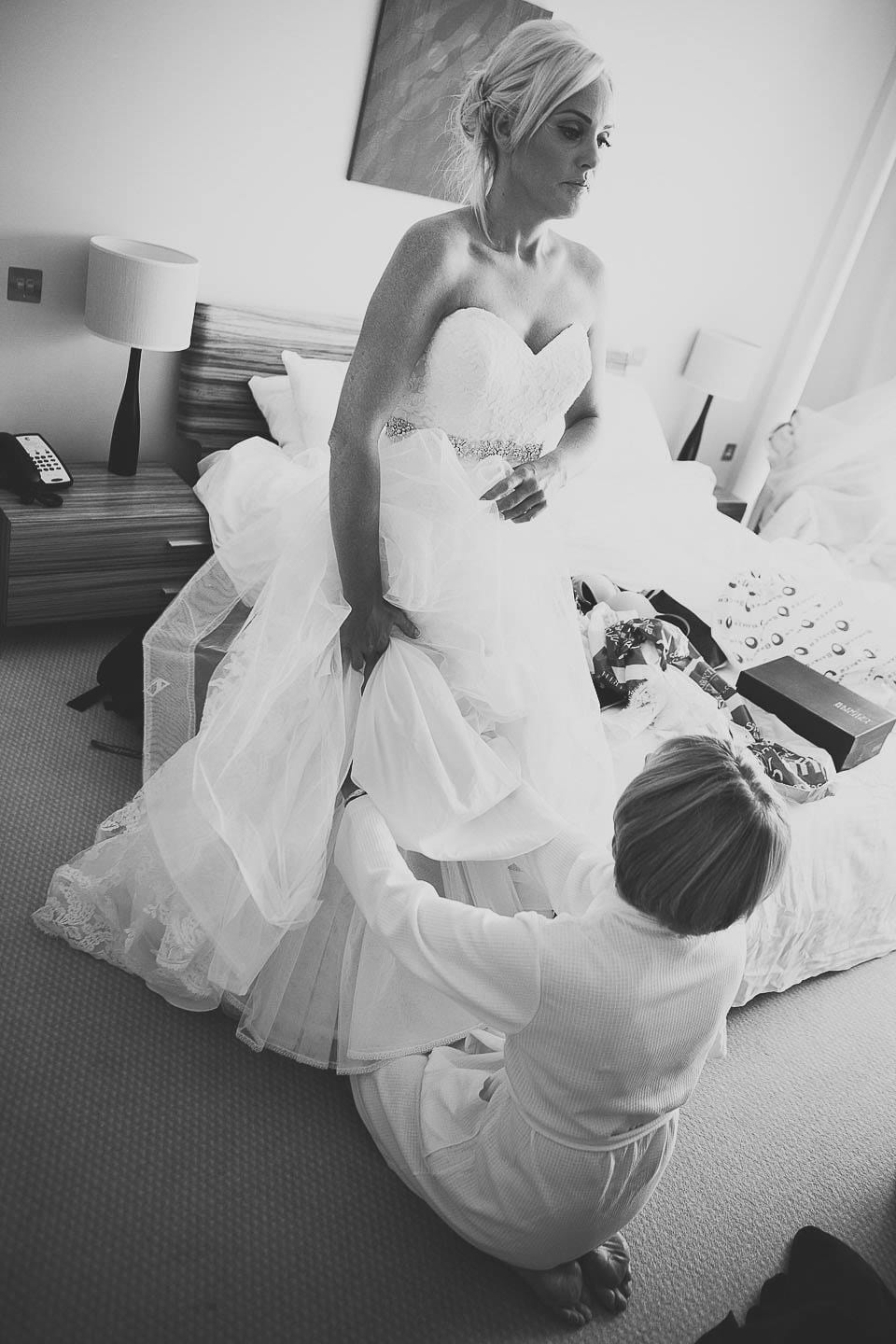 Mother of the bride helping bride put on her wedding dress at The Captains Club Hotel