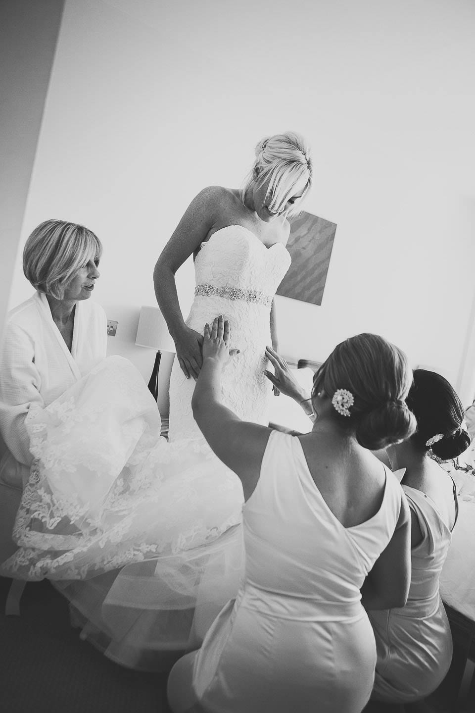Bridesmaids helping to arrange the wedding dress on the bride at The Captains Club Hotel