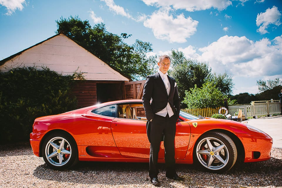 Groom standing by the Ferrari he drove for his wedding day at Sopley Mill